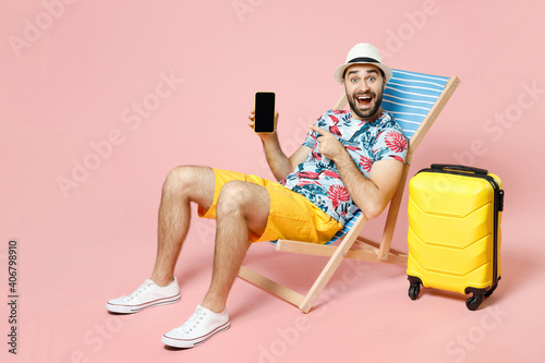 Fototapeta Full length amazed tourist man in hat sit on deck chair point index finger on mobile phone with blank empty screen isolated on pink background. Passenger travel on weekend. Air flight journey concept. obraz na płótnie