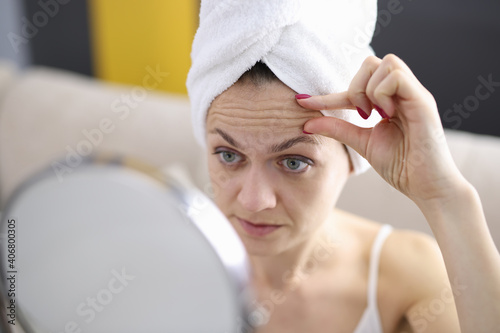 Obraz na plátně Woman examines her forehead wrinkles in mirror
