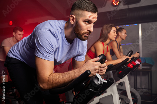 Obraz man biking in spinning class with friends at gym exercising on stationary bike, caucasian strong male is concentrated on workout - fototapety do salonu