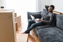An African-American Guy Chooses New Furniture Online In His New House Sitting On The Couch In Empty Living Room Among Cardboard Boxes, A Multiracial Man With Laptop On The Sofa At Moving Day