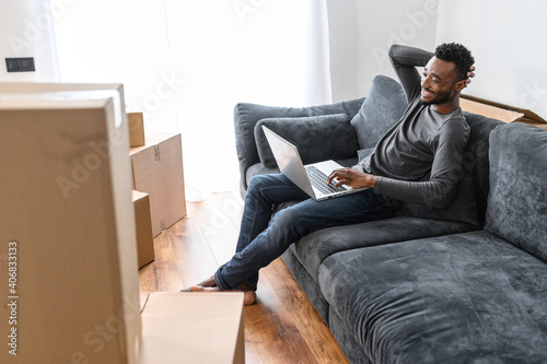 Fototapeta An African-American guy chooses new furniture online in his new house sitting on