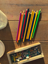 Top Above Overhead View Of A Table With A Set Of Coloring Pencils With A Variety Of Different Colors And A Chalk Box Full Of Small Colorful Chalk Pieces. Sunshine Casting A Shadow. Return To School.