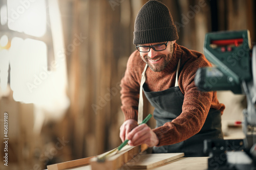 Fotografia brutal male carpenter working in  workshop