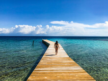 Beautiful Woman With Sculptural Body On Wooden Warehouse In Caribbean Sea With Clear Blue Water, Tranquility In Honduras, Roatan, Utila, Paradise Island