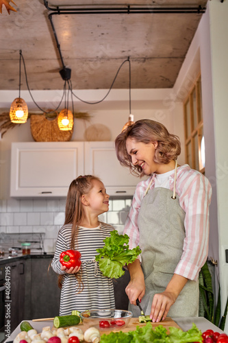 Obraz beautiful adult mother and daughter are going to prepare fresh salad together, having vegetables. food, family concept - fototapety do salonu
