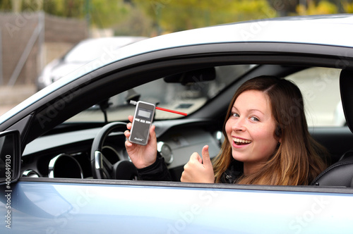 Photo drink and drive young female driver being subject to test for alcohol content with use of breathalyzer