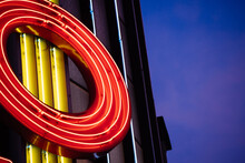 Vintage Neon Light Tubes Forming Letter O On The Metallic Roof Top With Dusk Blue Warm Color Skylight In Background