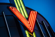 Vintage Neon Light Tubes Forming Letter V On The Metallic Roof Top With Dusk Blue Warm Color Skylight In Background