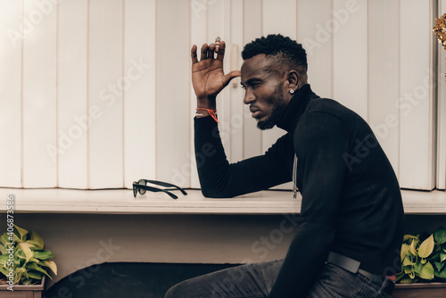 portrait of african model smoking cigar and posing for photography