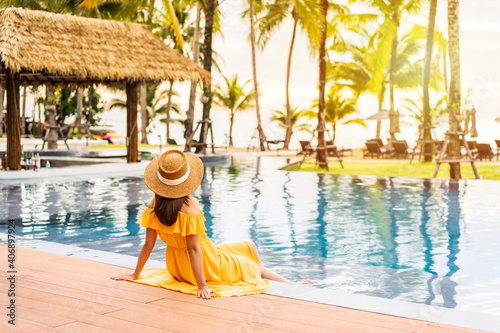 Photo Young woman traveler relaxing and enjoying the sunset by a tropical resort pool