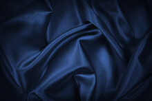 Abstract Blue Black Background. Navy Blue Silk Satin Texture Background. Beautiful Soft Wavy Folds On Shiny Fabric. Dark Elegant Background For Your Design.