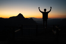 Silhouette Of Young Asian Man Standing On A Bench With Raising Fists To The Sky As A Winner While Admires The Fantastic Landscape Of Mountain Peaks With A Soft Golden Horizon Line On Sunset Or Sunrise