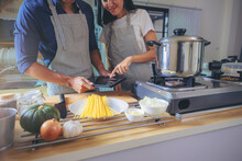 Happiness Asian Couple Using Smart Pad While Cooking In Kitchen Together At Home.