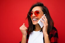 Closeup Photo Of Attractive Positive Smiling Young Brunet Woman Wearing Stylish Red Shirt White T-shirt And Red Sunglasses Isolated Over Red Background Communicating On Mobile Phone Looking To The