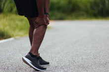 Asian Young Athlete Sport Runner Black Man Stand Wear Feet Shoe Active Running Training At Outdoor He Use Hands Hold On His Knee Pain While Running, Healthy Exercise Injury Osteoarthritis From Workout