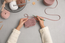 Woman Crocheting With Threads At Grey Table, Top View. Engaging Hobby