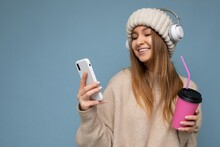 Attractive Happy Smiling Young Blonde Woman Wearing Beige Sweater And Beige Hat White Headphones Isolated Over Blue Background Holding In Hand And Using Mobile Phone Reading News Drinking Beverage And
