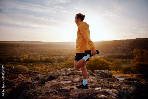 Obraz Male athlete doing leg stretching exercise preparing for run in nature trail at morning with sunrise view - fototapety do salonu