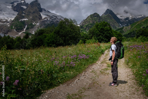 Man with backpack hiking in mountains. Travel Lifestyle success concept