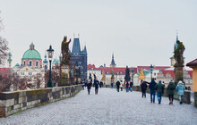 Prague, Czech Republic - January 7 2021: Occasional Tourists Take A Stroll Across Empty Charles Bridge