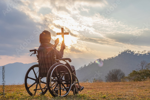 Leinwand Poster Disabled handicapped woman sitting on her wheelchair and hold the crucifix in ha