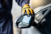 Male Auto Mechanic Hand Wearing Yellow Glove Adjusting Car Wing Mirror. Checking Car Part In Automotive Industry. Automobile Servicing And Repair Concept