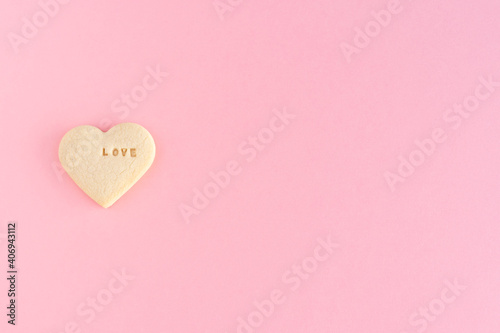 Fototapeta Heart shaped cookie with the word LOVE on a pink background Valentine's Day, Mother's Day, anniversary