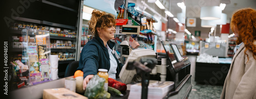 Photo Cashier assisting customer at supermarket checkout