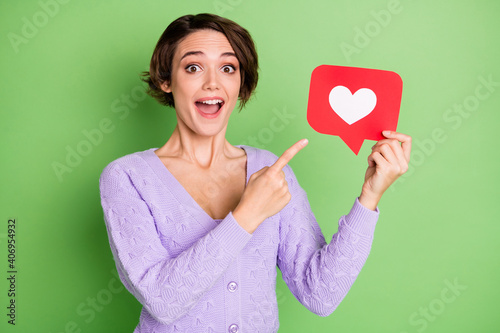 Portrait of astonished person open mouth direct finger paper heart like card isolated on green color background