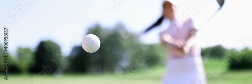Fotografia, Obraz Golf ball against background of hitting woman closeup
