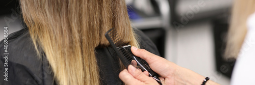 Tela Woman holds hair clipper in her hands
