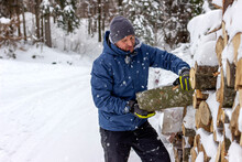 Portrait Of Smiling Handsome Young Man In Winter Forest Taking Logs For His Fireplace, Copy Space. Man Arranging Wood On Snowy Yard For A House Fireplace With Heavy Snowflakes Background.