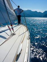 Sail Boat Yacht In Race Regatta With Sailor Crew Man With Mountain Background