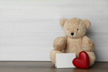Cute Teddy Bear With Heart And Blank Card On Wooden Table, Space For Text. Valentine's Day Celebration
