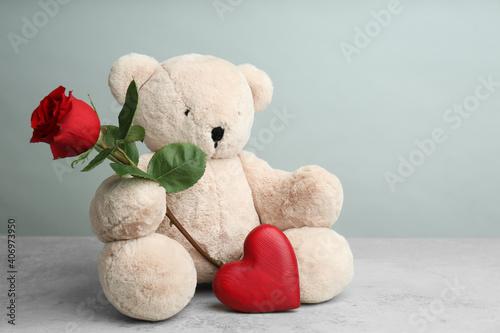 Obraz na plátně Cute teddy bear with heart and red rose on light grey stone table