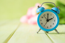 Spring Time Daylight Saving Concept - With Alarm Clock And Flowers, Copy Space