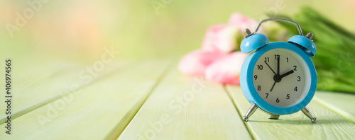Obraz Spring time daylight saving concept - with alarm clock and flowers, copy space - fototapety do salonu