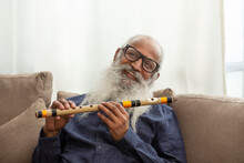 A HAPPY OLD MAN SITTING WITH FLUTE IN HAND