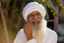 A HAPPY TURBANED MAN LAUGHING WHILE TWISTING MOUSTACHE