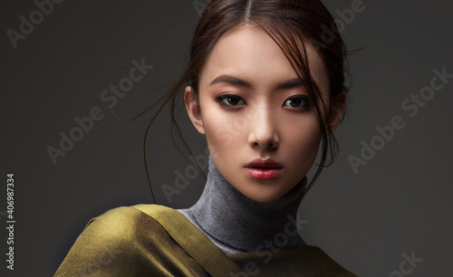 Obraz Beautiful Asian woman in a green shawl. Beauty of mysterious Chinese girl with flowing hair. Fashion, clothing and cosmetics - fototapety do salonu