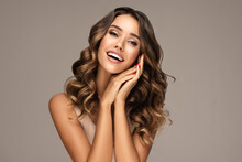 Beautiful Smiling Woman Holding Hands Near Face. Beauty Girl  With Curly Hair   . Presenting Your Product. Expressive Facial Expressions . Wavy Hairstyle. Beauty, Cosmetology And Cosmetics