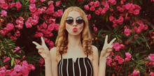 Portrait Of Beautiful Woman Blowing Her Red Lips Sending Sweet Air Kiss On A Pink Roses Flowers Background