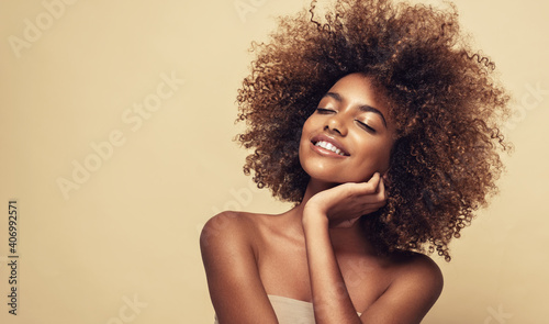 Beauty portrait of african american woman with clean healthy skin on beige background. Smiling beautiful afro girl.Curly black hair. Black teen girl