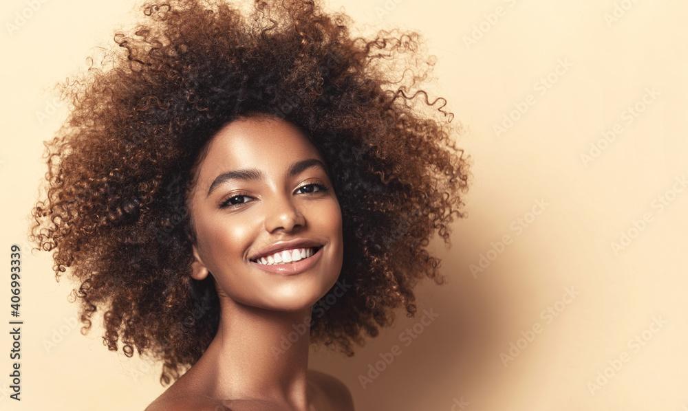 Fototapeta Beauty portrait of african american woman with clean healthy skin on beige background. Smiling beautiful afro girl.Curly black hair. Black teen girl