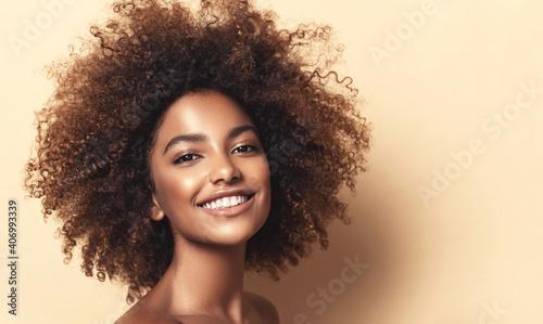 Fototapeta Beauty portrait of african american woman with clean healthy skin on beige background. Smiling beautiful afro girl.Curly black hair. Black teen girl obraz na płótnie