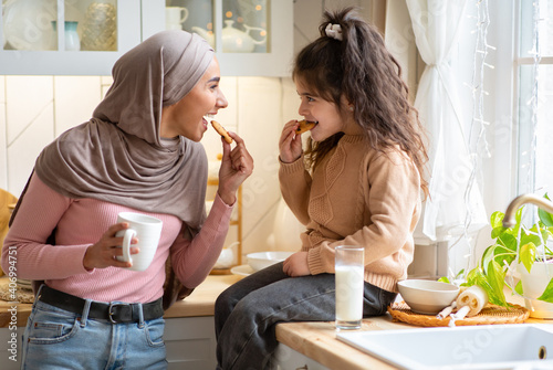 Obraz na płótnie Muslim Mom In Hijab And Her Little Daughter Eating Snacks In Kitchen