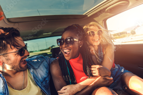 Obraz Three best friends enjoying traveling in the car, sitting in rear seat and having lots of fun on a road trip.	 - fototapety do salonu