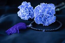 ライトブルーのカーネーションと数珠