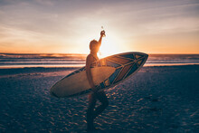 Woman With Surfboard Enoying Beer At Sunset After She Went Surfing