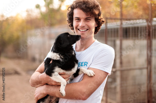 Fotografia Smiling kind man with dog in animal shelter